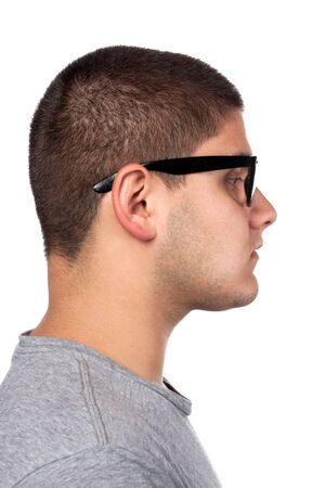 nerd glasses: A young teenage man isolated over white wearing black frame nerd glasses and military style dog tags. Stock Photo