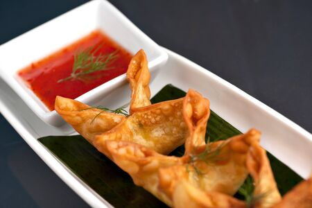 Fried thai crab cream cheese wontons or rangoons appetizer presented on a platter with fancy carrot and herb garnish. photo