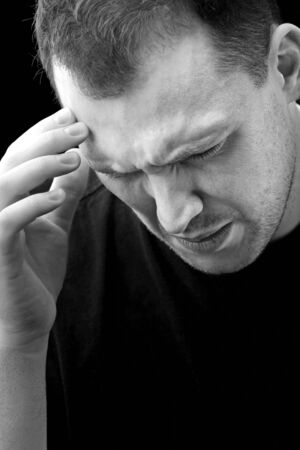 might: A man with an intense headache or migraine in black and white. He might be experiencing stress during a time of economic crisis or other hardship. Stock Photo