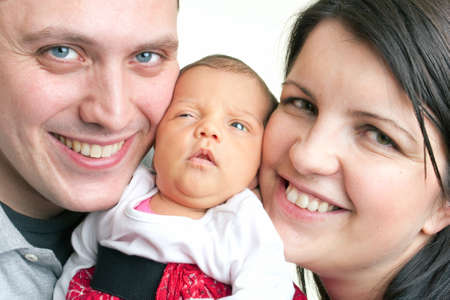 A young happy and healthy family  holding their newborn daughter between their cheeks. Stock Photo - 9589473
