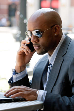 A business man in his early 30s talking on his cell phone and working on his laptop or netbook computer. Stock Photo - 9589307