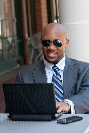 A handsome African American business man in his early 30s working on his laptop or netbook computer with his cell phone nearby. Stock Photo - 9589315