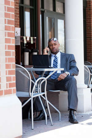 An African American business man in his early 30s talking on his cell phone and using his laptop or netbook computer. Stock Photo - 9589449