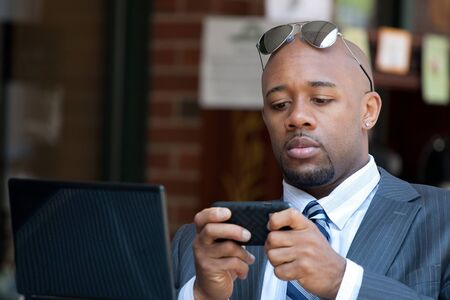 sms text: A good looking African American business man works on his laptop or netbook computer with a smart phone in his hands. Stock Photo