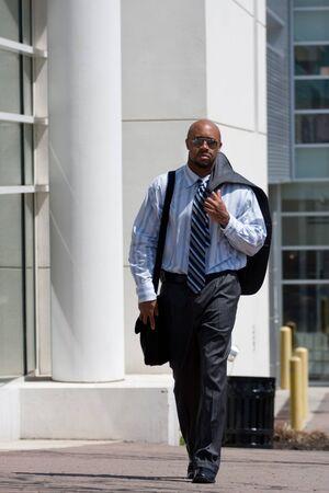 Un hombre de negocios seguros lleva su chaqueta de traje sobre su hombro mientras caminaba por la acera de la ciudad. Foto de archivo - 9589303