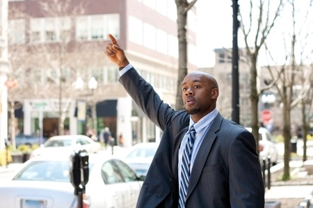 hail: An African American business man raises his hand to hail a cab in the city.