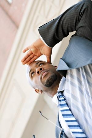 gaze: Een jonge zakenman geldt zijn hand op zijn voorhoofd als hij uit naar iets in de verte kijkt.
