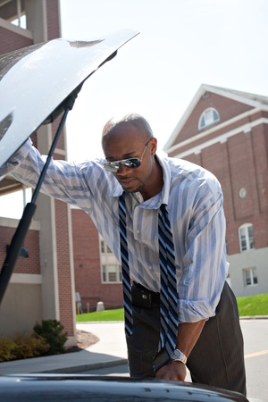 damaged cars: A business man having a bad day checks under the hood of his car to figure out what the problem is. Stock Photo