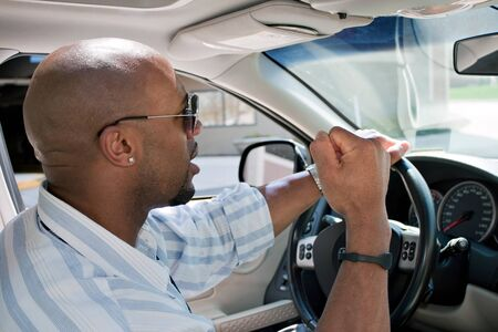 An irritated man driving a car is expressing his road rage with his fist clenched in the air.