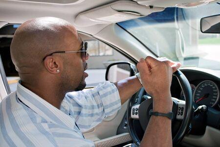 molesto: Un hombre irritado conduciendo un coche es expresar su furia con el pu�o cerrado en el aire. Foto de archivo