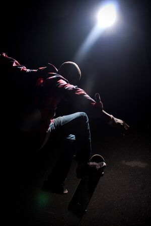 A skateboarder performs tricks under dramatic rim lighting with lens flare. Shallow depth of field.
