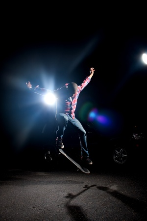 performs: Uno skateboarder esegue trucchi sotto illuminazione drammatica orlo con riflesso lente.  Archivio Fotografico