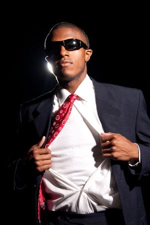 A young African American business man ripping his shirt open to reveal the t-shirt beneath. Add your text or artwork to easily customize the message. photo