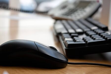 Close up of a modern office workplace desk setup with a computer mouse keyboard and phone. Shallow depth of field.
