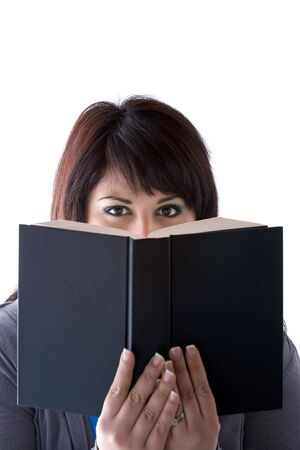 book: A young woman peeking over the top of a book she is holding up in front of her face.