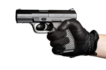 Close up of a persons hand wrapped in a leather glove gripping and aiming a semiautomatic handgun isolated over a white background. photo