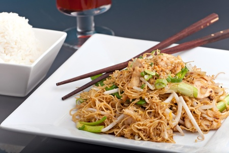 A Thai dish of chicken and noodles stir fry presented on a square white plate with wooden chopsticks. photo
