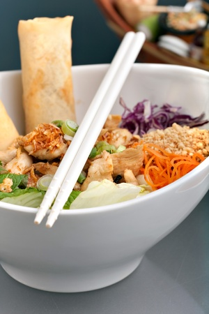 Freshly prepared Thai salad with spring rolls in a bowl with some chopsticks. Stock Photo - 9687745
