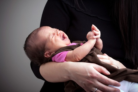 A mom holds a young newborn baby girl in her arms that is upset and crying. Stock Photo - 9687761