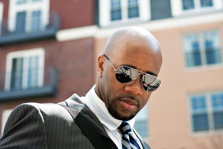 An African American business man wearing his sunglasses and business suit in the city.