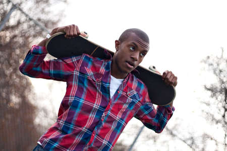 A young man hanging out holding his skateboard on the back of his shoulders over his head. photo