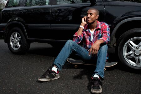 A young man hanging out sitting on his skateboard near his vehicle as he talks on his smartphone.