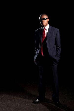 흑인 남자는 어두운 색된 양복과 선글라스 어두운 검정색 배경 앞에 서 옷을 입고. 스톡 콘텐츠