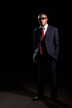 An African American man dressed in a dark colored suit and sunglasses standing in front of a dark black background. Stock Photo