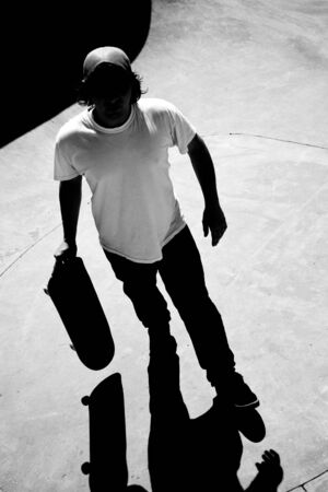 Silhouette of a skateboarder standing inside the pool at the skate park with strong contrast and dramatic shadows. Black and white. photo