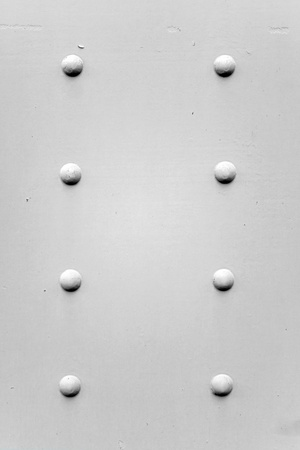 rivets: A painted metal background texture with four rusted bolts or rivets in black and white.
