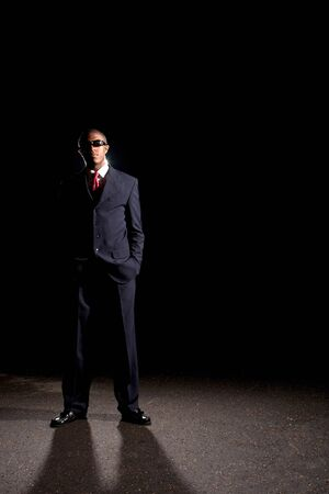 An African American man dressed in a dark colored suit and sunglasses standing in front of a dark black background. Foto de archivo
