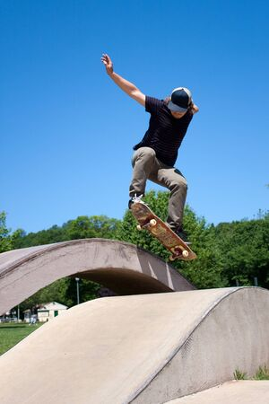 Action shot of a skateboarder performing a jump at a skate park. Stock Photo