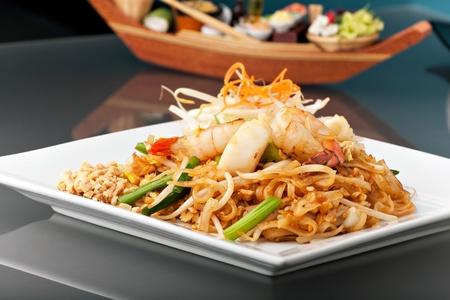 raton: Mariscos pad Thai plato de revuelo frito fideos de arroz en un plato cuadrado blanco con palillos y rallado guarnici�n de zanahoria. Foto de archivo