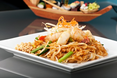 Seafood pad Thai dish of stir fried rice noodles on a square white plate with chopsticks and grated carrot garnish. Stock Photo