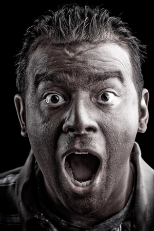 A frightened man with dark skin has a shocked or surprised look on his face.