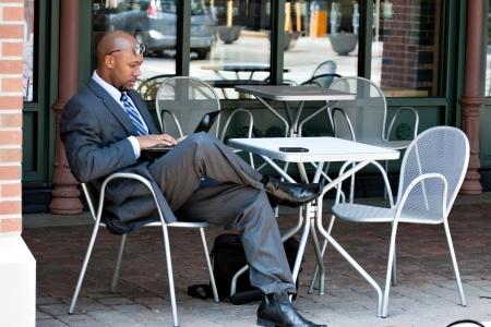 hombre sentado: Un hombre de negocios estadounidense en sus primeros 30 años con su ordenador portátil o netbook mientras está sentado en una mesa de café al aire libre.