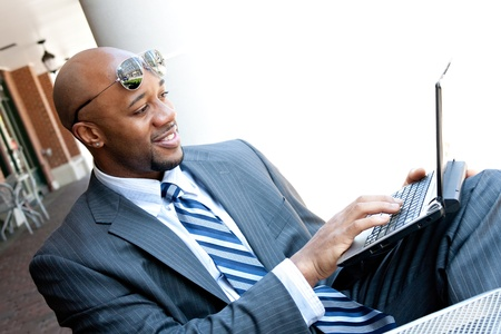 african business: An African American business man in his early 30s using his laptop or netbook computer outdoors with copy space for your text.