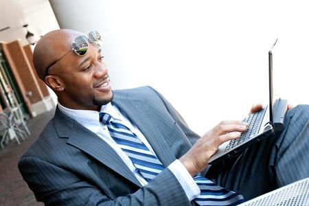 business man laptop: Un hombre de negocios estadounidense en sus 30s temprano utilizando su ordenador port�til o netbook al aire libre con espacio de copia para el texto.
