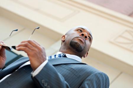 Een Afro-Amerikaanse zakenman zijn zonnebril en pak dragen in de stad.