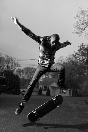 skateboarding tricks: A skateboarder performing jumps or ollies on asphalt.  Slight motion blur showing the movement on the arms and legs.