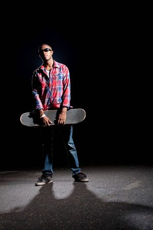 African American skateboarder wearing sunglasses holding his skateboard under dramatic lighting with dramatic shadows.   photo