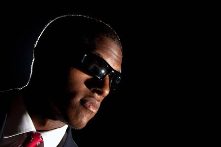 special agent: Low key portrait of an African American business man dressed in a suit and sunglasses standing in front of a dark black background.