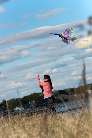 plus sized: A young brunette woman flies a kite at the beach on a nice day. Stock Photo
