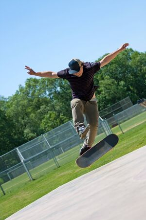 Action shot of a skateboarder doing tricks on his skateboard at the skate park. photo