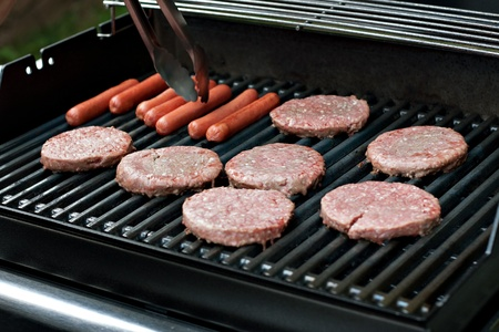 A closeup of some fresh and juicy hamburgers cooking on the grill. photo