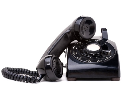 rotary dial telephone: An old black vintage rotary style telephone with the handset off the hook isolated over a white background.