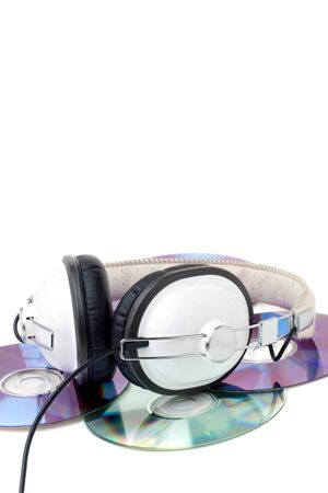 A set of stereo headphones laying on top a pile of compact discs isolated over white. Stock Photo - 10552642