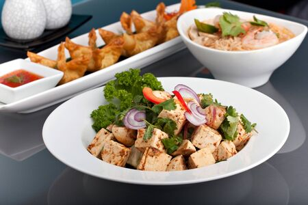 international food: A nice assortment of Thai food and appetizers presented beautifully with fancy garnish with copy space. Stock Photo