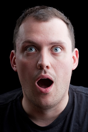 A shocked or surprised middle aged man over a dark background. photo