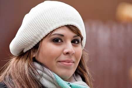 plus sized: A beautiful young Hispanic woman with a smile on her face wearing a winter buret style knit hat.
